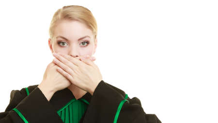 barrister: Confidential information. Law court or justice concept. Woman lawyer barrister wearing classic polish black green gown covering mouth with hands. Stock Photo