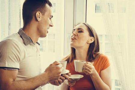 tea house: Happiness and healthy relationship concept. Attractive couple drinking tea or coffee together at home, man and woman holding cups with hot beverage at home