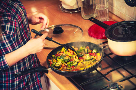 frozen food: Closeup of human in kitchen cooking stir fry frozen vegetables. Person frying making delicious dinner food meal. Stock Photo