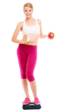 natural health: Young woman girl standing on weighing scale holding pills and apple. Choice between synthetic vitamins natural. Health care. Healthy lifestyle nutrition concept. Isolated on white .