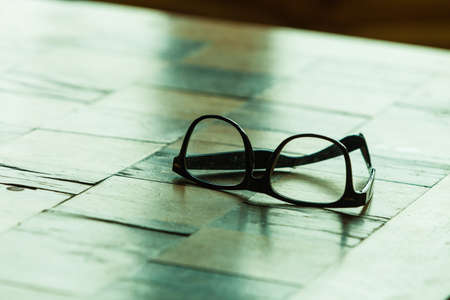contact lenses: Eyecare concept. Pair of stylish glasses on a checkered table Stock Photo