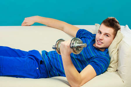 dumb bells: Relax after sport activity. Young man fit body relaxing on couch or having dreams of muscular body, dumb bell in hand