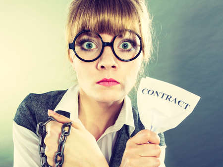 termination: Businesswoman woman ending agreement deal. Young girl holding chain breaking free creasing squeezing paper. Termination, breach of contract.