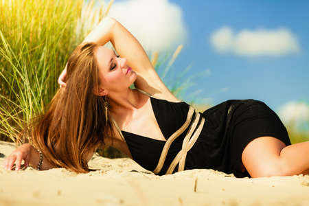 hot girl lying: Summer vacation day freetime concept. Sitting woman body sunbathing delight on beach seaside. Stock Photo
