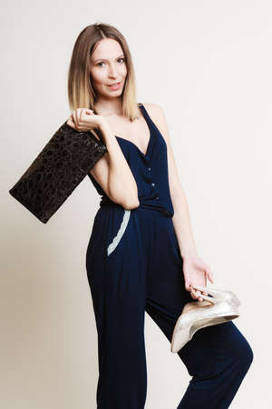 woman fashionable: Elegant outfit. Young stylish woman fashionable girl holding black handbag and silver high-heeled shoes on gray. Fashion and female beauty. Studio shot.
