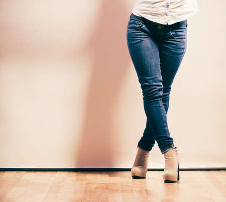 Fashion. Woman legs in denim trousers platform high heels shoes casual style studio shot, filtered photo