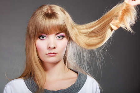dry hair: Haircare. Blonde woman with her damaged dry hair serious face expression gray background Stock Photo