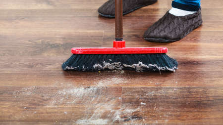 clean floor: Cleanup housework concept. Closeup broom and female foots. Cleaning woman sweeping wooden floor. Stock Photo
