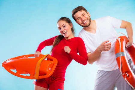 rescued: Accident prevention and water rescue. Young man and woman lifeguard couple on duty holding buoy lifesaver equipment having fun on blue Stock Photo