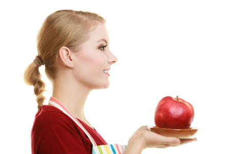 Diet and nutrition. Blonde young housewife or chef in striped kitchen apron offering red apple healthy fruit face profile isolated