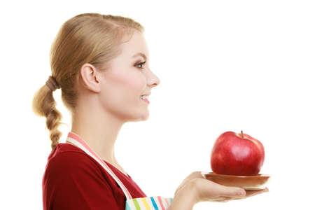 profil: Dieta i odżywianie. Blond młoda gospodyni lub kucharz w kuchni fartuch w paski oferujących czerwone jabłko zdrowe owoce profil twarzy wyizolowanych