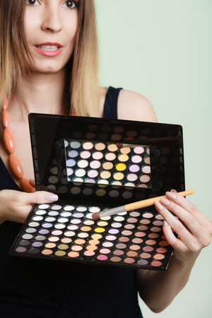 makeover: Cosmetic beauty procedures and makeover concept. Woman holds makeup professional palette and brush. Make-up applying with accessories tools. Green background