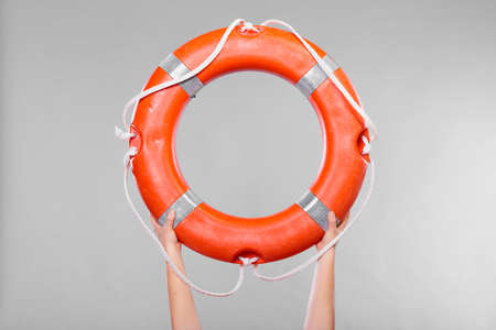 lifebelt: Accident prevention and water rescue. Life buoy ring lifebelt in female hands studio shot gray background