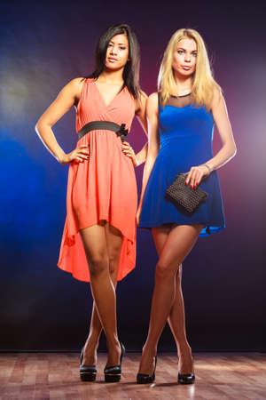 mujeres elegantes: Partido, celabration, carnaval. Dos mujeres elegantes atractivas de los vestidos de colores de fondo en el estudio. Foto de archivo