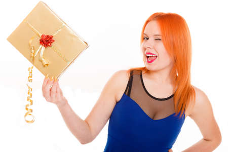 Christmas x-mas winter or valentine's day, birthday concept - red hair girl holding golden gift box winking studio shot isolated