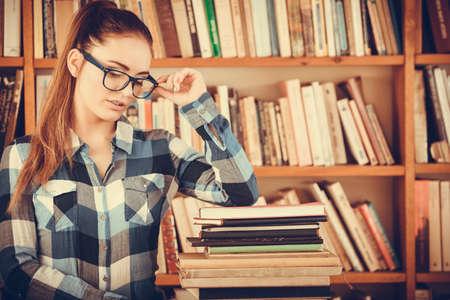 biblioteca: Concepto de la escuela de Educación. Chica a cuadros inconformista alumna camisa azul inteligente en la biblioteca de la universidad con libros de la pila