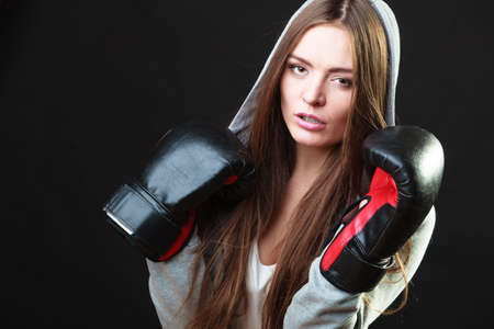 self defence: Martial arts or self defence concept. Sport boxer woman in gloves. Fitness girl training kick boxing on black background Stock Photo
