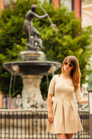 neptun: Holidays and tourism concept. pretty woman in elegant dress outdoor on the street of the old town european city Gdansk Danzig Neptune fountain Poland