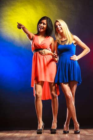 African dance: Partido, celabration, carnaval. Dos atractivas mujeres bailando divertidos en vestidos de colores de fondo en el estudio.