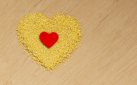 alkaline: Dieting healthcare concept. Millet groats heart shaped on wooden surface. Healthy food gluten-free and highly alkaline.