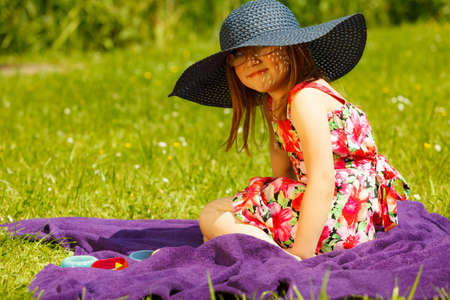 mother to be: Cute little girl wearing big summer hat pretending to be woman lady. Child imitate mother playing in park, outdoors Stock Photo