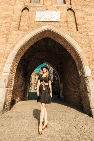 unusual angle: Unusual wide angle view of young woman in full length outdoors. Retro style fashion woman in black hat and dress on street of the old town european city Gdansk Danzig Poland