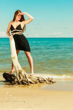 tanned girl: Holidays, vacation travel and freedom concept. Full length of beautiful sexy girl long hair on beach. Young pretty tanned woman in summer dress relaxing on the sea coast standing on dry tree root