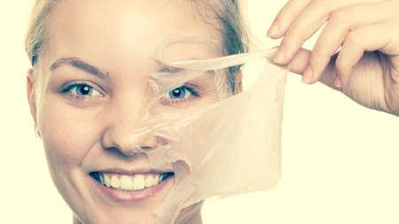 limpieza de cutis: Belleza cosm�ticos cuidado de la piel y el concepto de salud. Primer rostro de mujer joven, muchacha que quita facial mascarilla exfoliante. Peladura. Foto de archivo