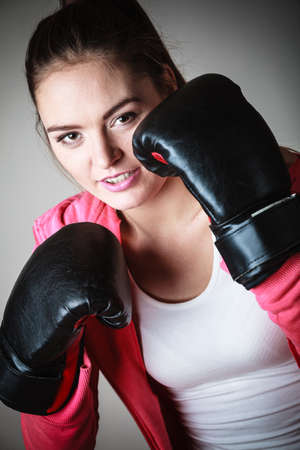 self defence: Martial arts or self defence concept. Sport boxer woman in black gloves. Fitness girl training kick boxing. Stock Photo