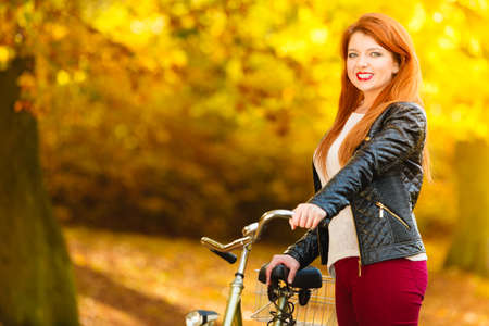 active lifestyle: Fall active lifestyle concept,. Beauty young redhaired woman fashion girl relaxing in autumn park with bicycle, outdoor Stock Photo