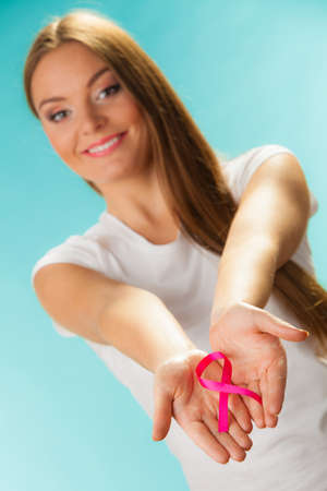 cancer treatment: healthcare and medicine concept - woman showing pink breast cancer awareness ribbon on hands on blue