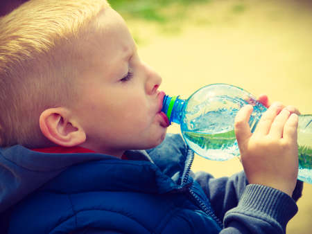 or thirsty: Poco sediento bebida ni�o ni�o de la botella pl�stica, al aire libre