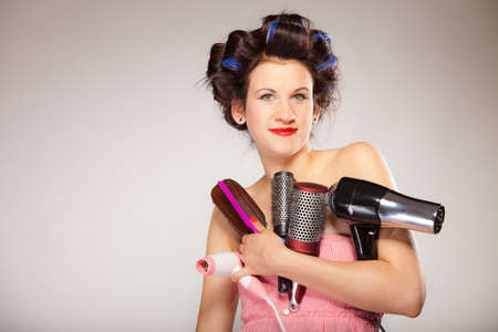 drier: Young woman preparing for date having fun, cute girl with curlers styling hair with many accessories comb brush hairdreyer on  gray