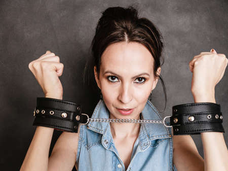 manacles: Arrest and jail. Criminal woman prisoner girl showing leather handcuffs on gray. Punishment.