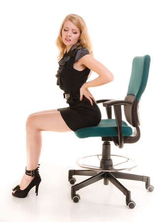 soreness: Young businesswoman with backache. Blonde woman with back pain sitting on chair. Long working hours and health.  Business.