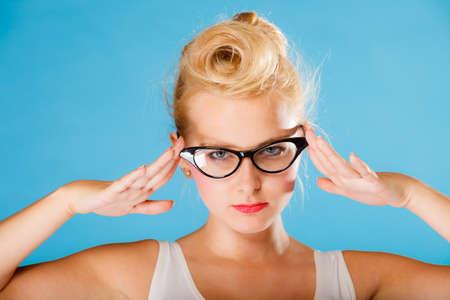 oculist: Optometrista, oculista y el concepto oftalmólogo. Joven rubia retro pin up mujer con gafas en el fondo azul en el estudio. Foto de archivo