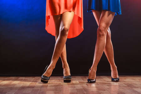 disco girls: Party, celebration, disco concept. Women in evening dresses dancing in the club, part of body female legs in high heels on party floor.