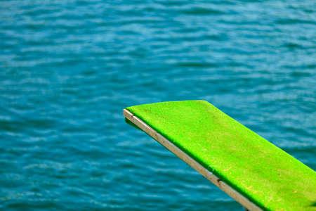 springplank: Zomervakantie en gevaarlijke sport. Uitzicht op duikplank. Springplank om te duiken in het water.