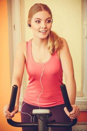 escucha activa: Active joven que se resuelve en la bici de ejercicio en bicicleta estacionaria. Formaci�n Muchacha deportiva en casa escuchando m�sica. Fitness y concepto de p�rdida de peso. Instagram se filtr�.