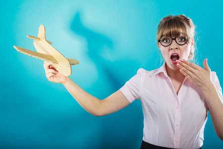 lady fly: Fly fear metaphor, aerophobia concept. Business woman holding airplane in hand vivid blue background