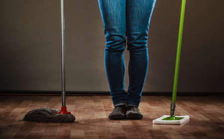 mops: Cleanup housework concept. Cleaning woman legs, girl mopping floor, holding two mops new and old dark background