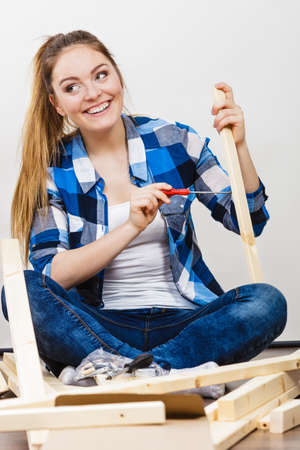 woman chest: Woman assembling wooden furniture using screwdriver. DIY enthusiast. Young girl doing home improvement.