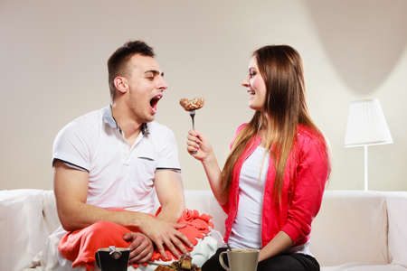 caloric: Smiling woman feeding happy man with cake. Wife and husband eating caloric food.