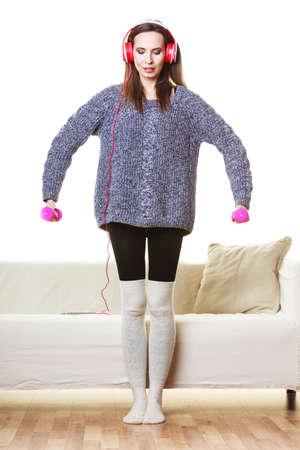 escucha activa: Estilo de vida activo, relajarse concepto. Montar una mujer de escuchar m�sica mientras hace ejercicio con pesas en casa Foto de archivo
