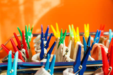 laundry line: Housework concept. Closeup of clothes hanging to dry on a laundry line with colorful pegs clips indoor