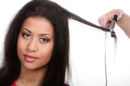 hairstyling: Hairstyling. attractive mixed race woman with long hair making hairstyle hairdo with electric hair curler iron on white Stock Photo