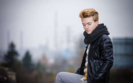 cityspace: Street fashion. Young fashionable man guy with stylish hair posing outdoors on cityspace background