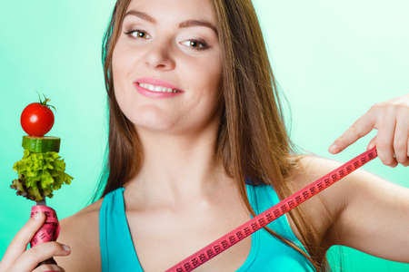to the diet: Dieting weight loss concept. Sporty girl fitness woman holding fork with fresh mixed vegetables and measuring tape on green blue background.