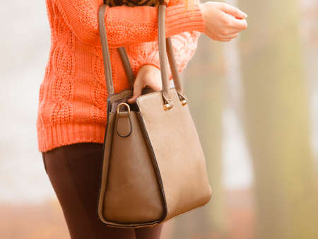 Autumn fashion. Woman fashionable girl wearing vivid clothing holding brown leather bag handbag in hand, walking in autumnal foggy park, outdoors