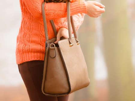 handbag: Autumn fashion. Woman fashionable girl wearing vivid clothing holding brown leather bag handbag in hand, walking in autumnal foggy park, outdoors